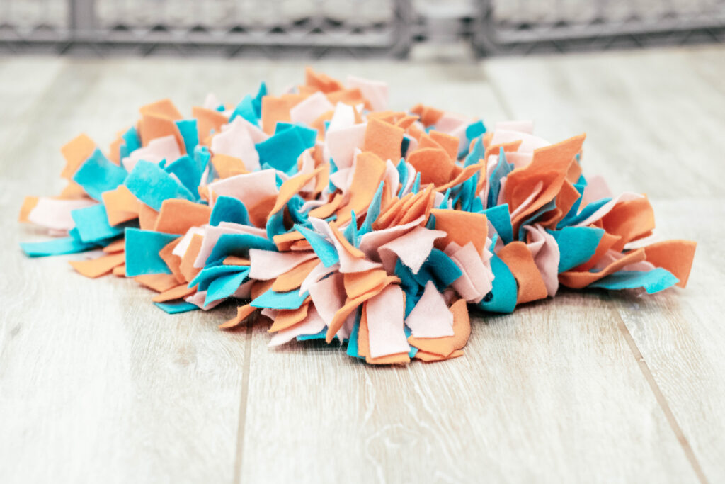 photo of the DIY snuffle mat on the floor with orange, teal and light pink fabric