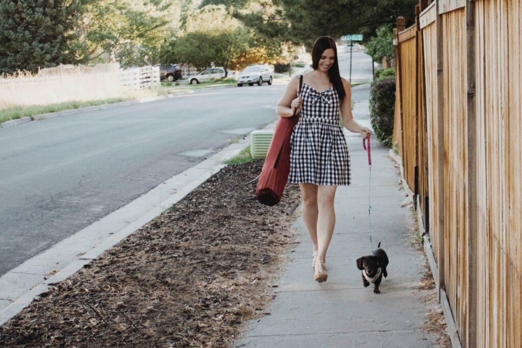 A lady walking her dog down the sidewalk with an eco friendly dog leash.