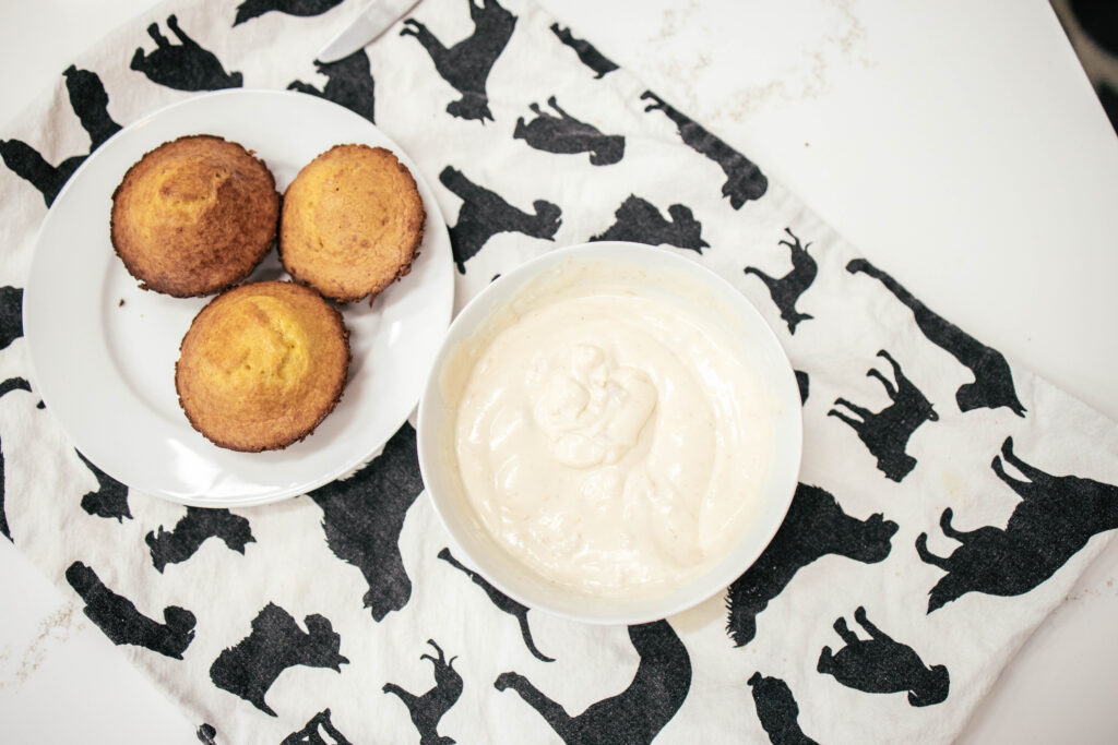 Three small dog cakes on a plat with a bowl of the dog friendly frosting