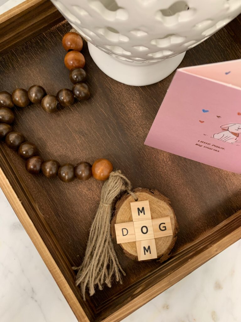 Beaded garland on tray that says dog mom in tile scrabble letters