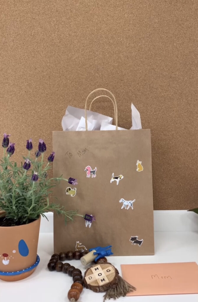DIY pet gift for Mother's Day paper gift bag decorated with dog stickers that says too mom on a table