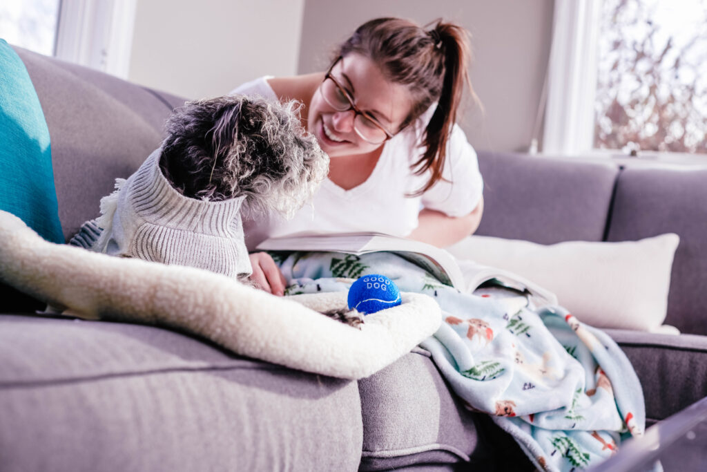 Dog on couch with woman leaning in talking with heads together